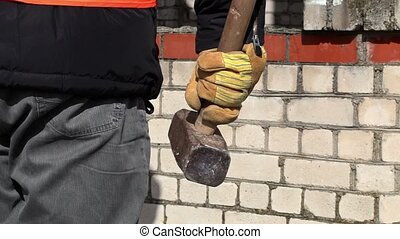 Worker with sledgehammer near