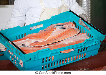 Worker With Sliced Fishes In Crate - Midsection of worker...