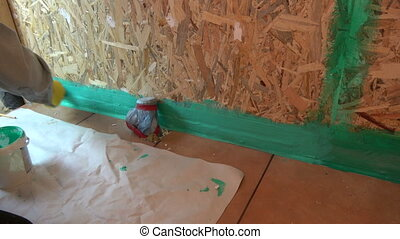Worker with small paintbrush waterproofing bathroom...