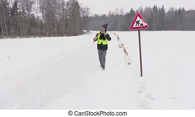 Worker with snow shovel in snowy day near road sign