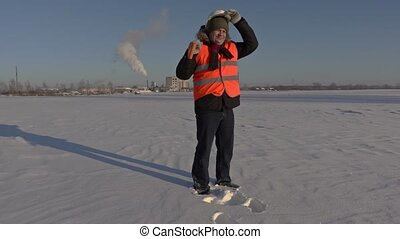 Worker with snow shovel walking to the factory