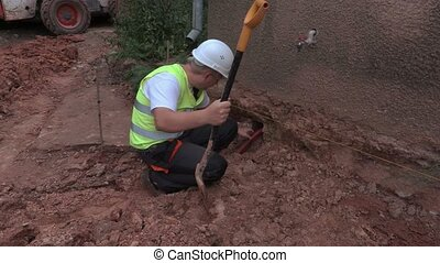 Worker with spade at the base of the house