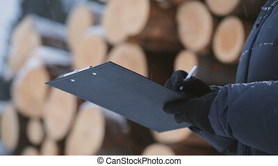 Worker with tablet against pile of logs