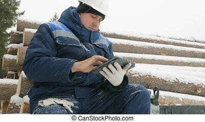 Worker with tablet computer on big pile of logs in winter forest