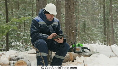 Worker with tablet computer working in winter forest
