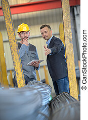 worker with tablet talking to manager in a warehouse