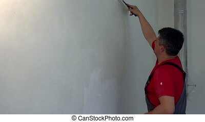 Worker with trowel spackling wall with filler. Static shot