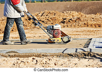 worker with vibration compactor - builder worker at sand...