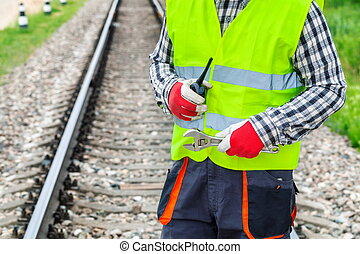 Worker with walkie talkie and wrench on railway