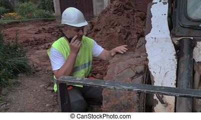 Worker with walkie talkie near tractor tire