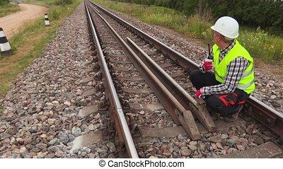 Worker with walkie talkie sitting on rails