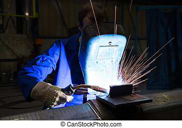 Worker with welding helmet welds steel