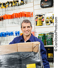 Worker With Wrapped Package In Hardware Shop
