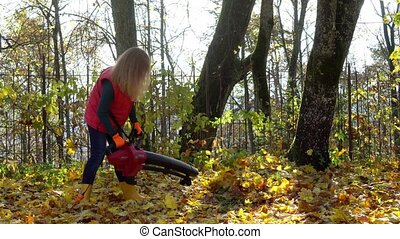 Worker woman wearing red jacket and yellow gumboots blowing autumn leaves with leaf blower machine. Gimbal motion shot.