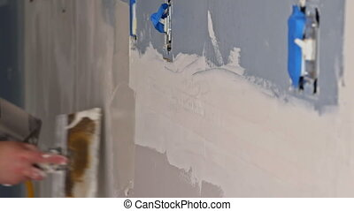 Worker working with putty and spatula work aligns with wall