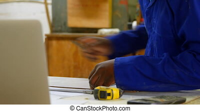 Worker working at table in workshop 4k