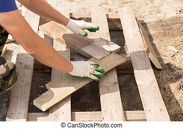 worker working with wooden planks at construction site