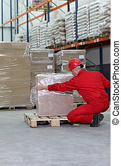 worker wrapping box on wooden pallet in warehouse - back...