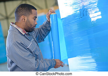 worker wrapping up merchandice in warehouse