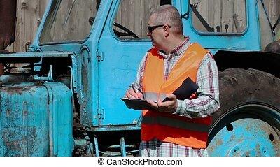 Worker writes near tractor