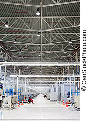 Workers adjust machines in factory shop