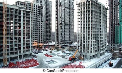 Workers and building materials at construction site in foreground of cityscape