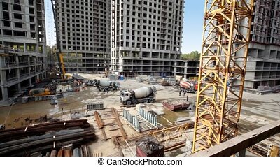 Workers and concrete mixers at construction site of many houses