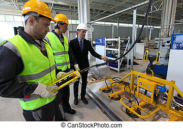 Workers and lifting device - Manager and workers near metal...