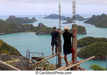 Workers are building on a top of the mountain on the island