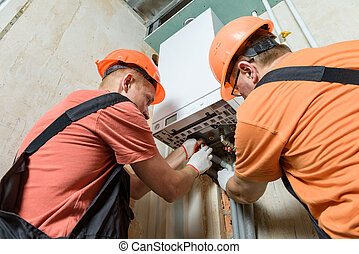 Workers are connecting the pipes to the gas boiler.