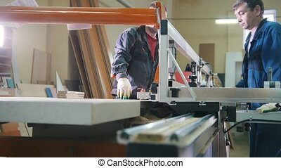 Workers are cutting wooden detail on electric saw at...