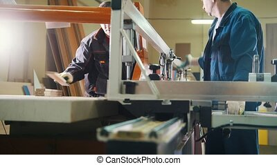 Workers are cutting wooden fragment on electric saw at...