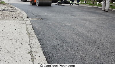 Workers are leveling hot asphalt after is applied on the...
