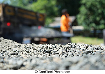 Workers are mixing hot stone caused by burning. Mixed with high temperature asphalt In order to repair the road (blurred images)