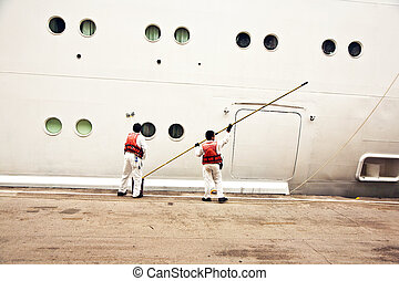 workers are painting the ships body