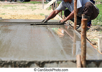 Workers are plastered concrete in the sun.