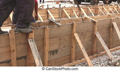 Workers are pouring fresh concrete in vertical wooden mold...
