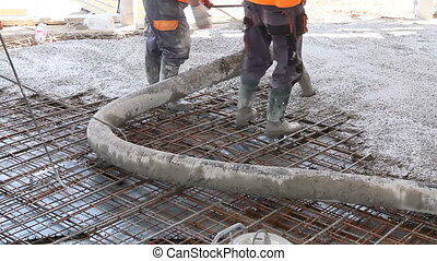 Workers are spreading concrete over big reinforced floor on...