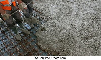 Workers are spreading concrete over big reinforced floor on the construction site