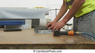 Workers assembling two objects - Side view mid section of a ...
