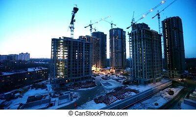 Workers at construction site in foreground of dormitory area cityscape