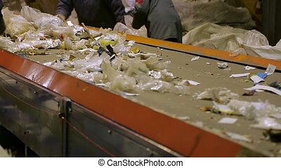 Workers at conveyor sorting garbage at a recycling plant....