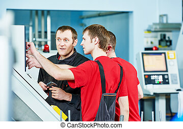 workers at manufacture workshop - three industrial workers...