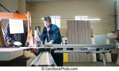 Workers carpenters are cutting wood board on electric saw at furniture factory