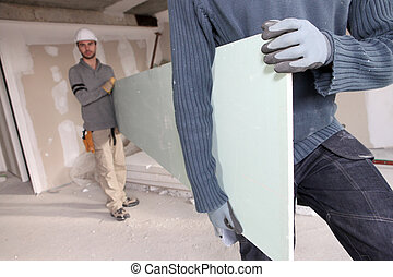 Workers carrying plasterboard