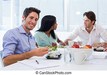 Workers chat and smile to camera while enjoying lunch in the...