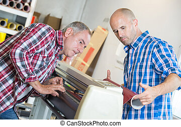 workers checking a printer format inkjet working