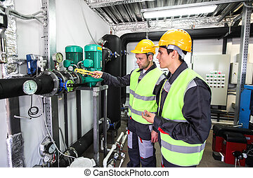 Workers checking parameters of pressure