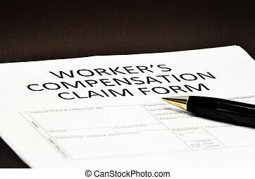 Worker's compensation claim form application with pen on desk