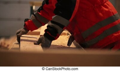 Workers control process of sawing and polishing wooden boards at the sawmill